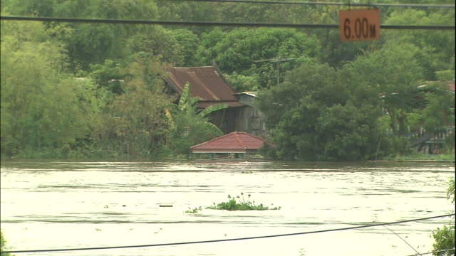 Residents of Ayutthaya walk flood waters of the swollen Chao Phraya River