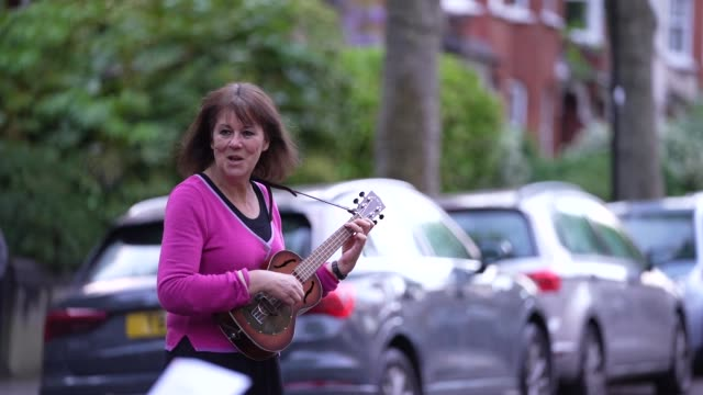 "residents of crouch end sing along as a man and woman perform ""get by with a little help from my friends"" by the beatles, following the weekly ""clap... - performance stock videos & royalty-free footage"