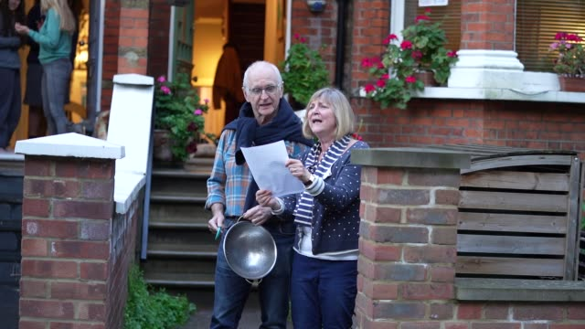"""residents of crouch end sing along as a man and woman perform """"get by with a little help from my friends"""" by the beatles, following the weekly """"clap... - performance stock videos & royalty-free footage"""