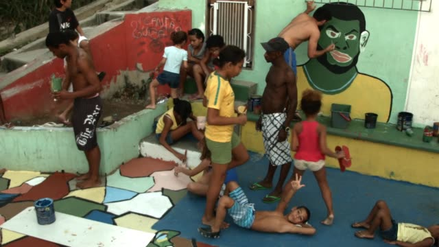 residents of santa marta favela paint football themed murals in preparation for the upcoming fifa 2014 world cup, shot in rio de janeiro, on the 8th... - ゴールを狙う点の映像素材/bロール