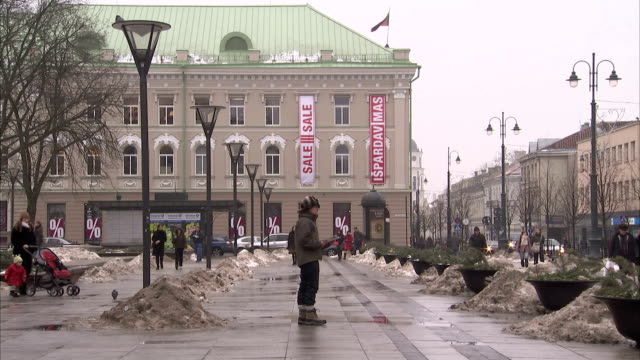 residents of siauliai walk through a plaza where snow stands in piles. available in hd. - lithuania stock videos & royalty-free footage