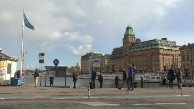 residents of stockholm walk in the city centre, and public buses and ferries take people home at rush hour in the early evening - stockholm stock videos & royalty-free footage