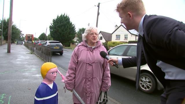 Residents oppose childlike traffic bollards ENGLAND Buckinghamshire Iver Heath EXT Traffic bollard in shape of child as cars past Close shot child...