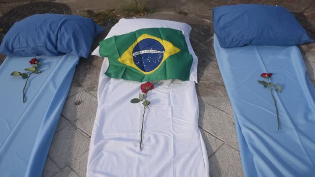 residents place roses on mattresses symbolizing covid-19 victims, during a protest against the government's handling of the covid-19 pandemic,... - död koncept bildbanksvideor och videomaterial från bakom kulisserna
