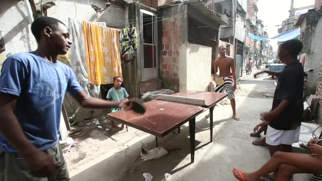 ls residents play table tennis in the mare favela complex currently occupied by the army ahead of the 2014 fifa world cup on june 7 2014 in rio de... - 陸軍点の映像素材/bロール