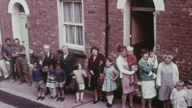 vidéos et rushes de ds residents posing in front of row houses and waving / exeter, england, united kingdom - 1970