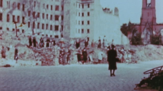 stockvideo's en b-roll-footage met residents shoveling up rubble from destroyed buildings with a bucket brigade, and traffic and pedestrians on a city street / berlin, germany - geruïneerd