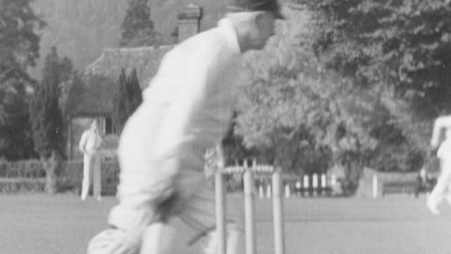 1938 montage residents sitting and watching a cricket match in the village green, with a terrier dog stealing the ball and running away, dodging the fielding team / leominster, england, united kingdom - cricket video stock e b–roll