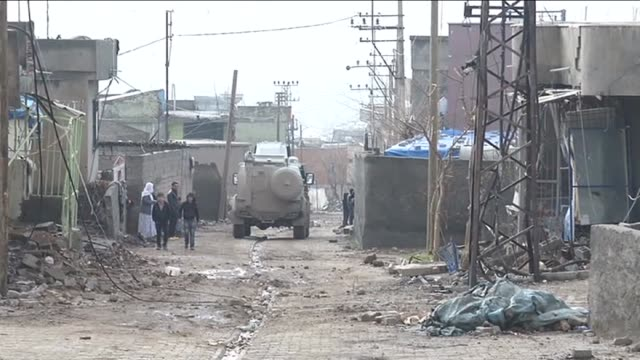 residents walk on a damaged road after the curfew ended in the silopi district of sirnak turkey on january 19 2016 some of the streets and many... - silopi stock videos and b-roll footage