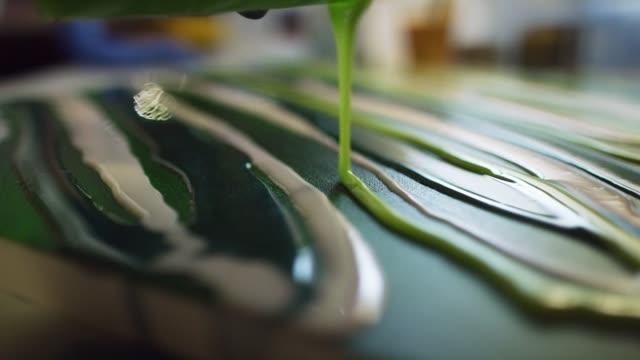 vídeos y material grabado en eventos de stock de un artista de resina con guantes vierte resina de epoxy verde sobre un lienzo pintado en un estudio de arte interior - acrílico