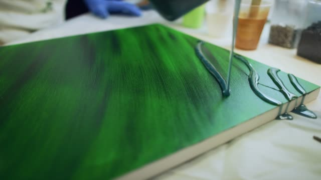 a resinista / artist with safety gloves pours green epoxy/resin over a painted canvas in an indoor art studio - art studio stock videos & royalty-free footage