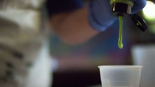 a resinista squirts green acrylic paint from the tube into a plastic cup - squirting stock videos and b-roll footage