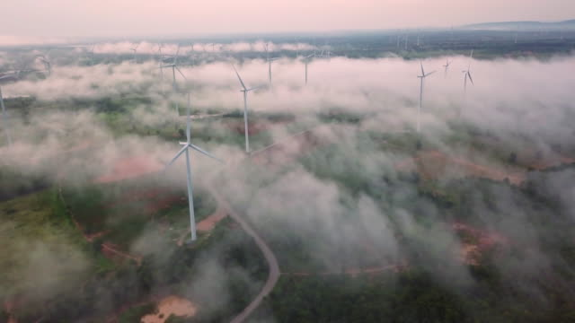4K Resolution Aerial view of Wind Turbine field on fog and mist over landscape,Eolic park,wind power and Alternative Energy concept