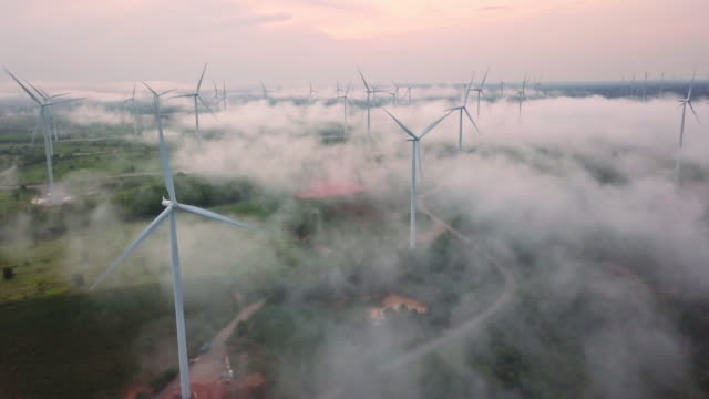 4k resolution aerial view of wind turbine field on fog over landscape,eolic park,wind power and alternative energy concept - origins stock videos & royalty-free footage