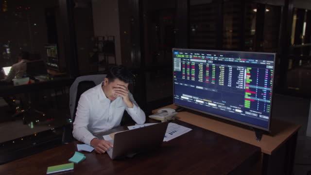 4k解像度アジアのビジネスマンは、暗闇の中でオフィスでコンピュータラップトップの前でテーブルの上に真剣な行動で遅く働き、考えています, ビジネス金融と投資の概念.遅くまで働き、� - 心配する点の映像素材/bロール