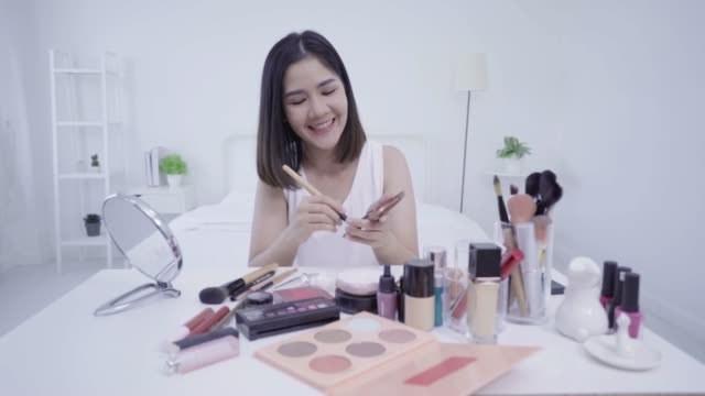 4k resolution asian woman beauty blogger,v-logger applying brusher to her face doing cosmetic makeup tutorial - tutorial stock videos and b-roll footage