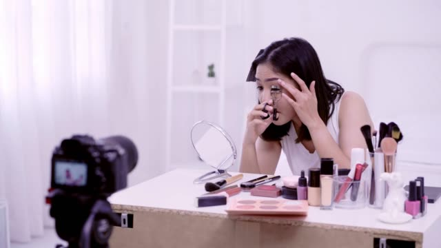 4k resolution asian woman beauty blogger,v-logger applying eyelash curler to her eye doing cosmetic makeup tutorial - tutorial stock videos and b-roll footage
