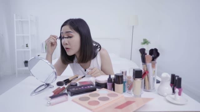 vídeos y material grabado en eventos de stock de 4k de resolución mujer asiática belleza blogger, rimel aplicación v registrador para su ojo haciendo tutorial de maquillaje cosmético - cámara de televisión
