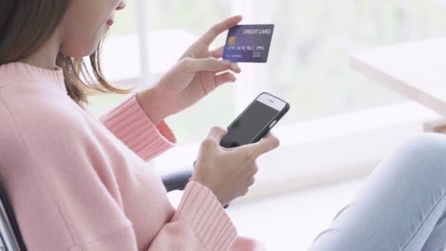 4 k 解像度のアジア女性の電話はクレジット クレジット カードでオンライン ショッピングを利用して - 注文する点の映像素材/bロール