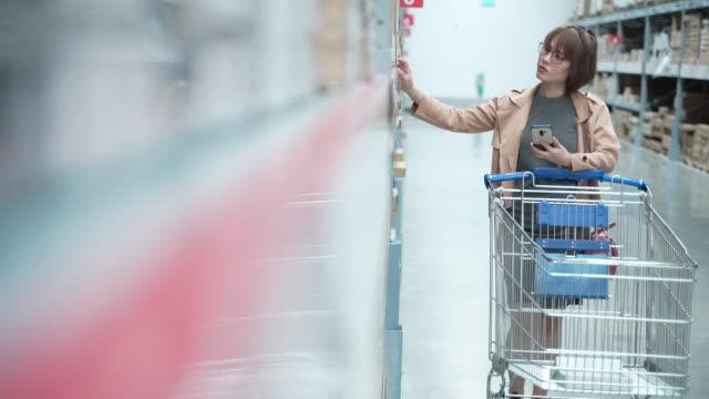 4k解像度アジアの女性は、storeでスマートフォンのショッピングを見ています。女性は製品を選択します。アジアの女の子は物を買っている - shopaholic点の映像素材/bロール