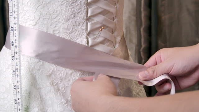 4k resolution close up the dressmaker is sewing the wedding dress. - sposa video stock e b–roll