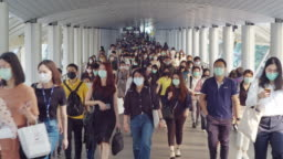 4K resolution crowds of Asian people wearing face protection in prevention for Coronavirus or Covid-19 and micro dust pm 2.5 in air while going to their workplace in Bangkok at morning rush hour