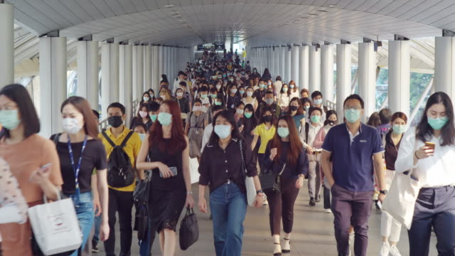 4k resolution crowds of asian people wearing face protection in prevention for coronavirus or covid-19 and micro dust pm 2.5 in air while going to their workplace in bangkok at morning rush hour - busy stock videos & royalty-free footage