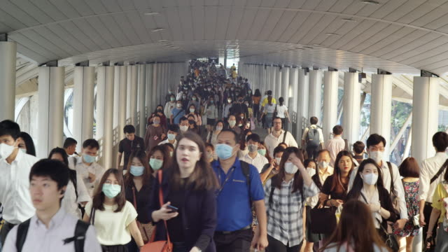 4k resolution crowds of asian people wearing face protection in prevention for coronavirus or covid-19 and micro dust pm 2.5 in air while going to their workplace in bangkok at morning rush hour - pedestrian crossing stock videos & royalty-free footage