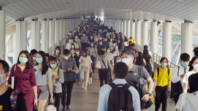 朝のラッシュアワーにバンコクの職場に行く間、コロナウイルスまたはcovid-19とマイクロダストpm 2.5の予防で顔保護を身に着けているアジアの人々の4k解像度の群衆 - 風邪点の映像素材/bロール