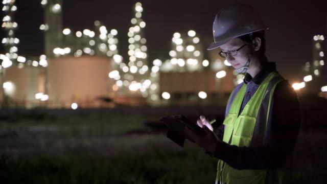 4k 解像度エンジニア石油化学アジア人男性は、夜に精製石油・ガス産業工場内のスマートタブレットで遅く、ハードワーク - 有害廃棄物点の映像素材/bロール