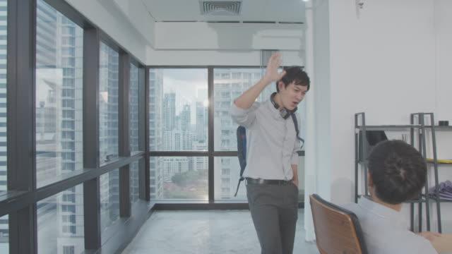 vidéos et rushes de 4k résolution images funny handsome jeune homme d'affaires gai et marchant tout en saluant collègues, style de vie de bureau asiatique heureux - collègue