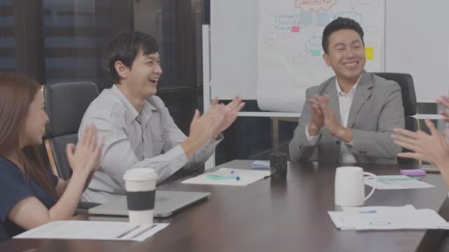 stockvideo's en b-roll-footage met 4k-resolutie gelukkig aziatische business team lachen en klappen in viering in indoor modern kantoor, aziatische business life - feliciteren