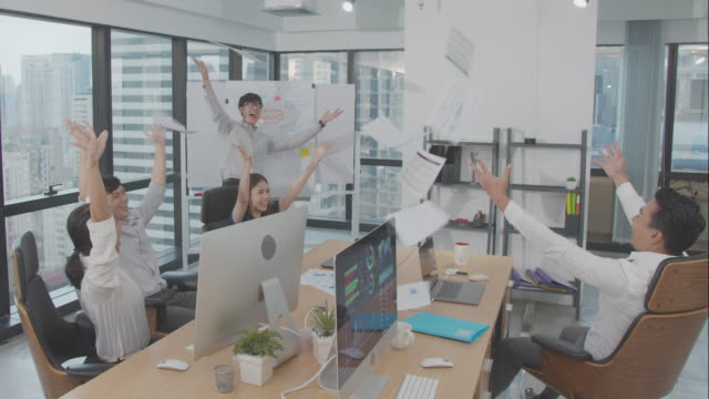 4k resolution happy asian business team laugh and clapping in celebration in indoor modern office,asian business life - aspirations stock videos & royalty-free footage