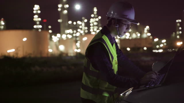 4k resolution happy engineer petrochemical asian man work late and hard with laptop computer  inside the refinery oil and gas industry factory at night.engineering work successfully - toxic waste stock videos & royalty-free footage