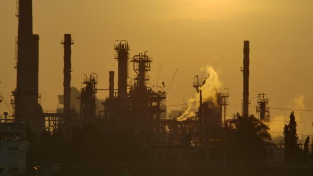 vídeos de stock, filmes e b-roll de refinaria de óleo da definição 4k na manhã no nascer do sol com estrutura da silhueta da reflexão da chaminé da liberação do gás da conduto - pulverizando