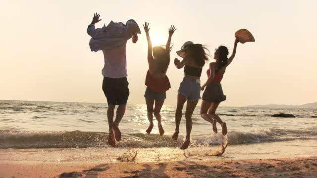 日没時にビーチで走ってジャンプして楽しんでいる混合レースの友人の4k解像度リアビューグループ。ライフスタイルの友人は、休暇の夏のコンセプトを旅行します。スローモーションショ� - 背中点の映像素材/bロール