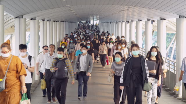 vídeos de stock e filmes b-roll de 4k resolution slow motion shot of crowds of asian people wearing face protection in prevention for coronavirus or covid-19 and micro dust pm 2.5 in air while going to their workplace in bangkok at morning rush hour - proteção