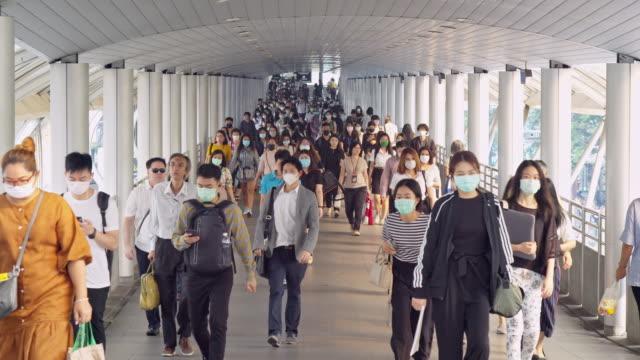 朝のラッシュアワーにバンコクの職場に行っている間、コロナウイルスまたはcovid-19とマイクロダストpm 2.5の予防で顔保護を身に着けているアジアの人々の群衆の4k解像度スローモーションシ - 安全衛生保護具 マスク点の映像素材/bロール