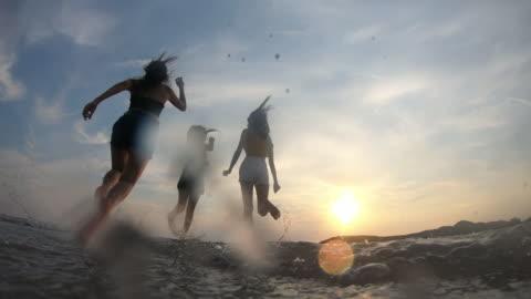 vidéos et rushes de résolution 4k slow-motion asiatique femme heureux groupe amis profiter de vacances d'été et drôle courir sur la plage - plage