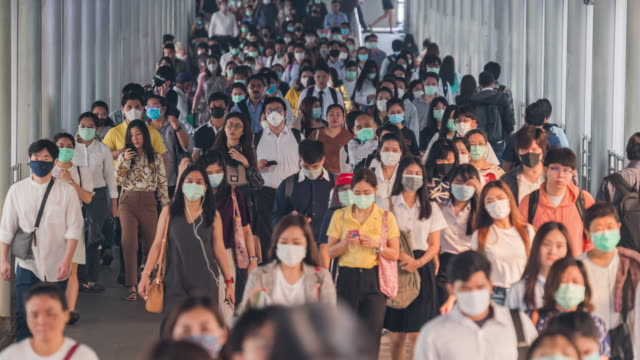 4k resolution time lapse  crowds of asian people wearing face protection in prevention for coronavirus or covid-19 and micro dust pm 2.5 in air while going to their workplace in bangkok at morning rush hour - crowded stock videos & royalty-free footage