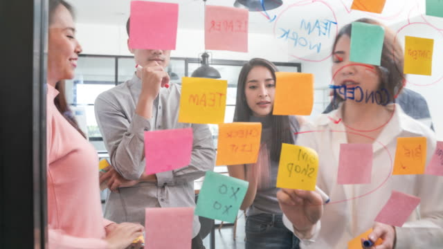 4k resolution time-lapse of asian young creative team brainstorm meeting  and writing down ideas on sticky notes attached to glass wall in modern office,business colleague coworker meeting and sharing idea concept - organization stock videos & royalty-free footage