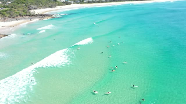 4k resolution video of surfers riding waves in clear ocean waters cabarita beach, new south wales, australia - natural arch stock videos & royalty-free footage