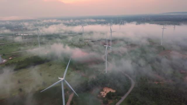 4k-upplösning vind turbin fält på dimma och dimma över landskap, vindkraft och alternativ energi koncept - kulle bildbanksvideor och videomaterial från bakom kulisserna