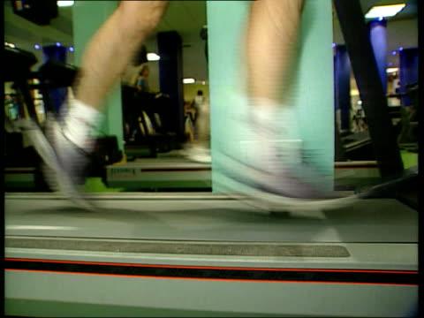 resolutions lib london legs running treadmill in gym cigarette stubbed out in ashtray - zigarettenstummel stock-videos und b-roll-filmmaterial