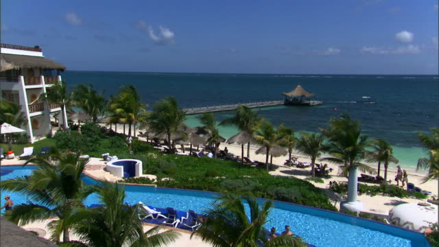 a resort at puerto morelos overlooks a swimming pool and the ocean. - urlaubsort stock-videos und b-roll-filmmaterial