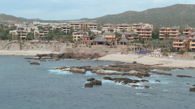 resort buildings surround a swimming pool. - cabo san lucas stock videos & royalty-free footage