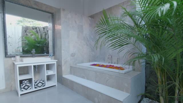 a resort hotel spa bathroom bathtub with flowers. - privatsphäre stock-videos und b-roll-filmmaterial