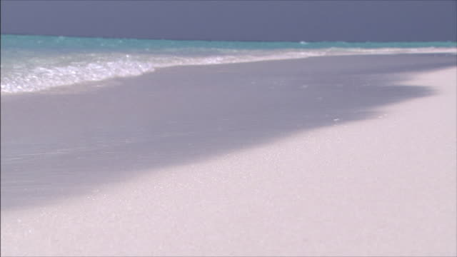 vidéos et rushes de resort island blue sea and white beach water's edge close shot - transparence