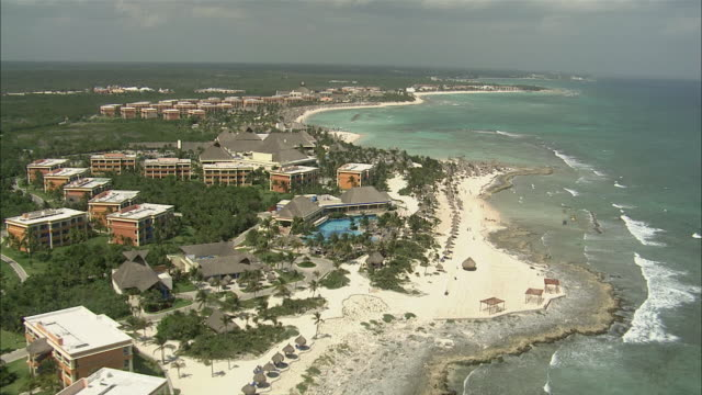 aerial resorts along coast with white sand beaches and clear, blue water, swimming pools and buildings with maya pyramid style / cancun, quintana roo, mexico - mexico stock videos & royalty-free footage