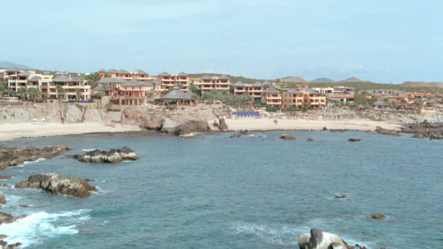 resorts rise above a beach in mexico. - cabo san lucas stock videos & royalty-free footage